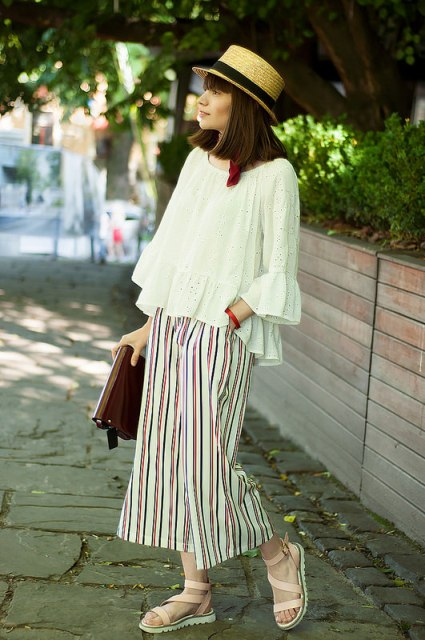 With white loose ruffle shirt, hat, beige sandals and clutch