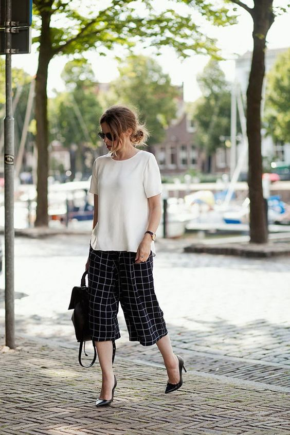 checked black and white culottes, a white top, black heels and a backpack to work