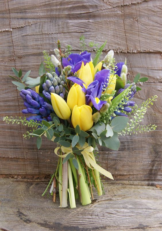 a bridal bouquet of yellow tulips, purple iris, green thlaspi, blue hyacinth and pussy willow