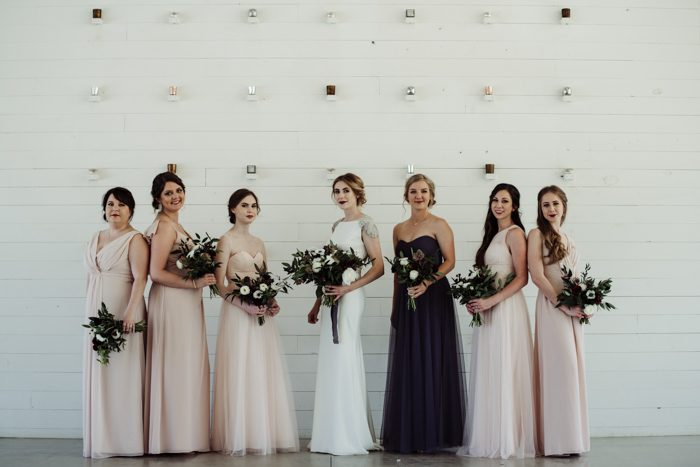 The bridesmaids were wearing light pink mismatching dresses, and the maid of honor was wearing a purple dress
