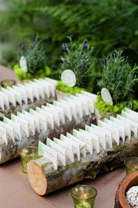 a rustic card display with wooden logs with moss and escort cards on them