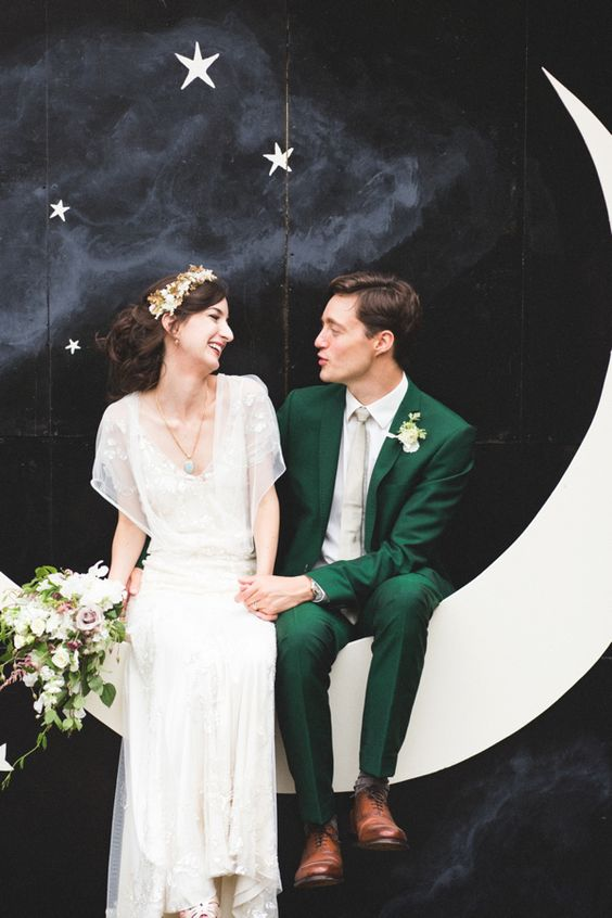 a black night sky with stars and a crescent moon wedding photo booth backdrop for a vintage feel