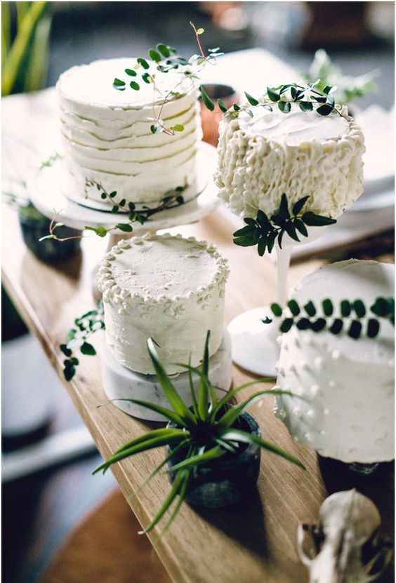an assortment of white textural wedding cakes with fresh greenery on top