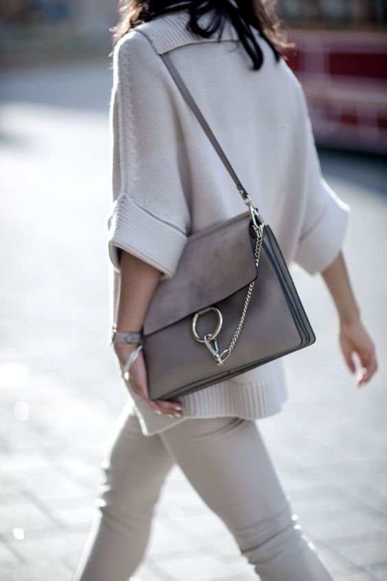a gorgeous grey leather bag with a large metal ring and a chain plus a leather handle for any occaison