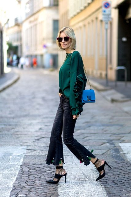 With emerald shirt, flare pants, heels and blue bag