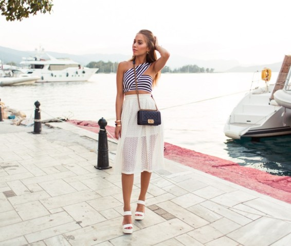 With white airy skirt, white sandals and black chain strap bag