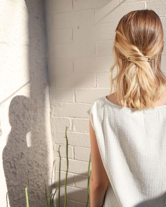 a simple criss cross half updo secured with a minimalist barrette