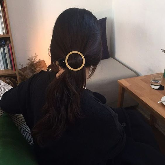 a low ponytail with a metallic barrette is a stylish idea
