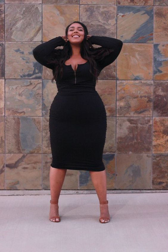 a black midi fitting dress, long sleeves and a zip neckline, brown shoes
