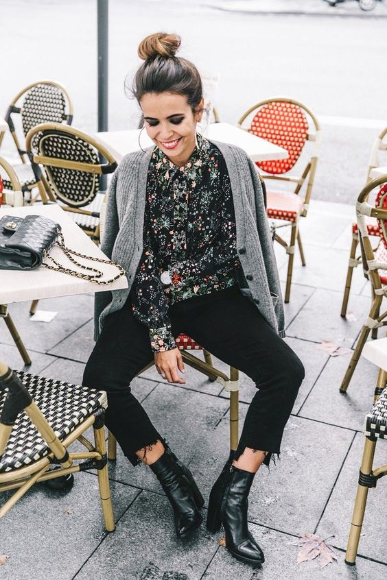 black boots, a floral shirt, black raw edge jeans and a grey cardigan