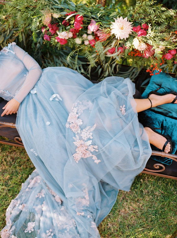 The bride was earing a light blue wedding gown with a sheer bodice, long sleeves and a train, with tender pink floral appliques
