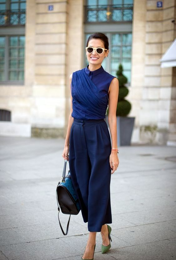 navy culottes, a navy sleeveless blouse with buttons, green heels for an exquisite look