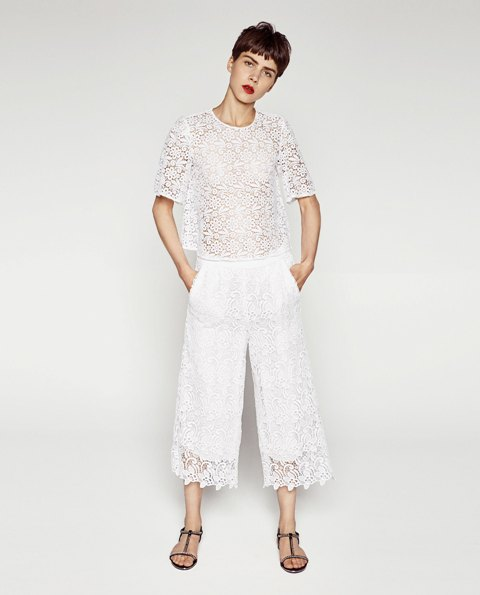 With lace shirt and flat sandals
