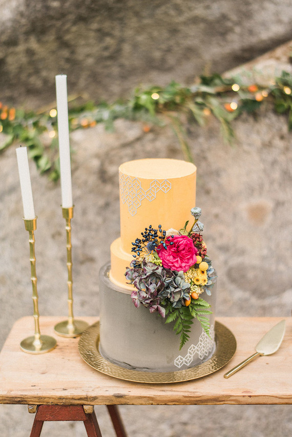 The wedding cake was done in grey and yellow and with bold blooms on the side