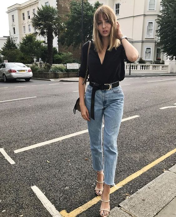 a black blouse, light blue high waisted raw hem jeans and metallic strappy shoes