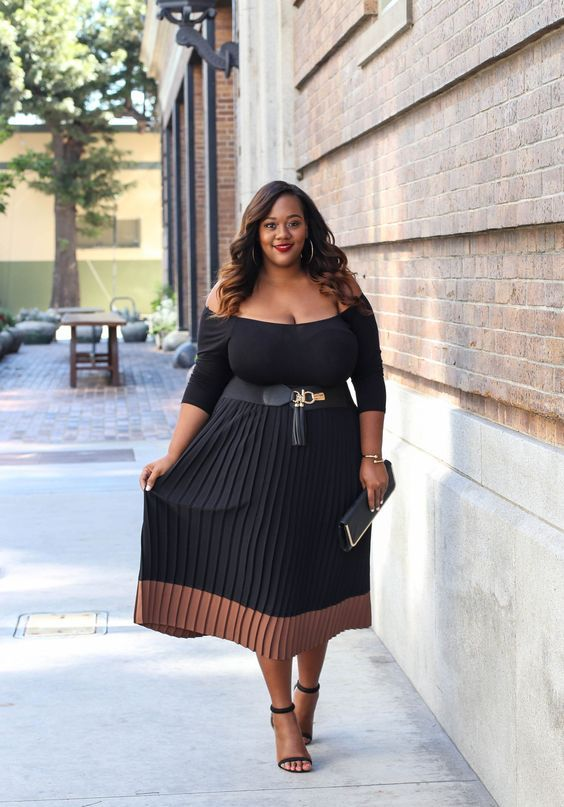 a black off the shoulder midi dress with a color block effect and a pleated skirt, a clutch and heels