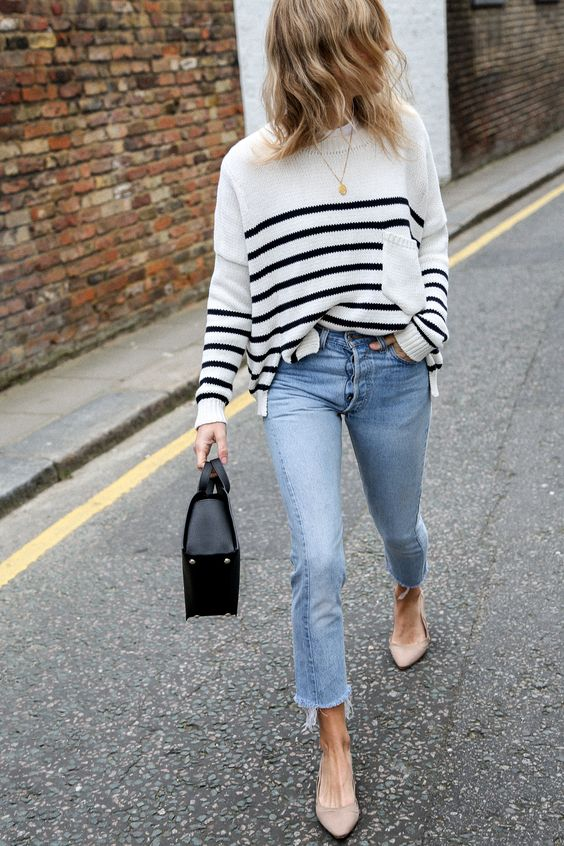 a striped white and black sweater, light blue raw edge jeans, nude flats and a black bag