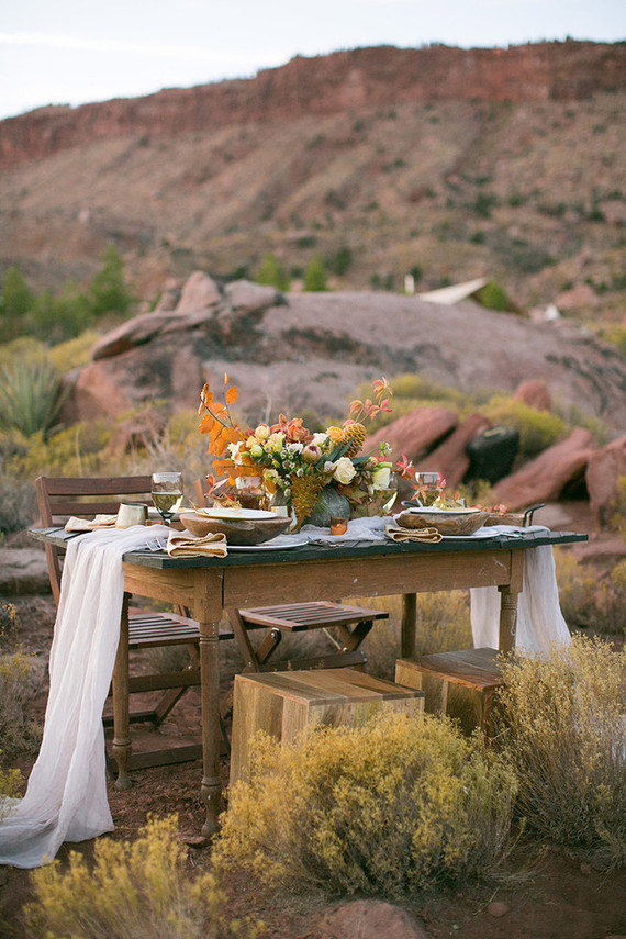 The wedding table setting was done with an airy table runner, with a lush fall-inspired boho floral centerpiece