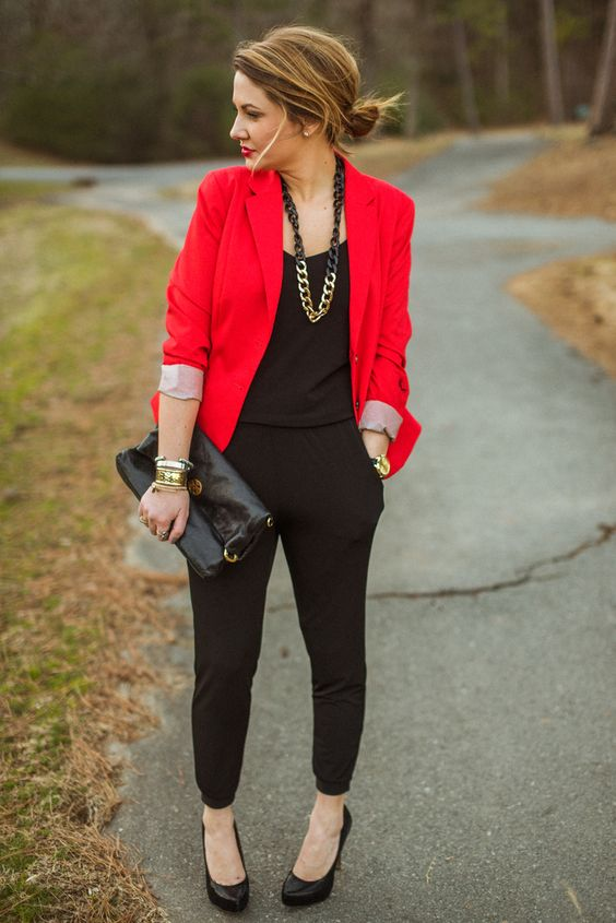 a black jumpsuit, black heels and a clutch, a statement chain necklace and a red blazer