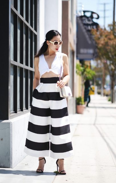 With white top, black high heels and white chain strap bag