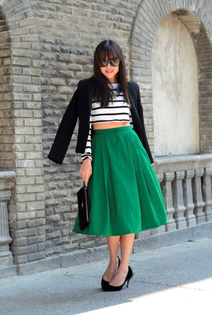 With green skirt, black pumps, black blazer and clutch