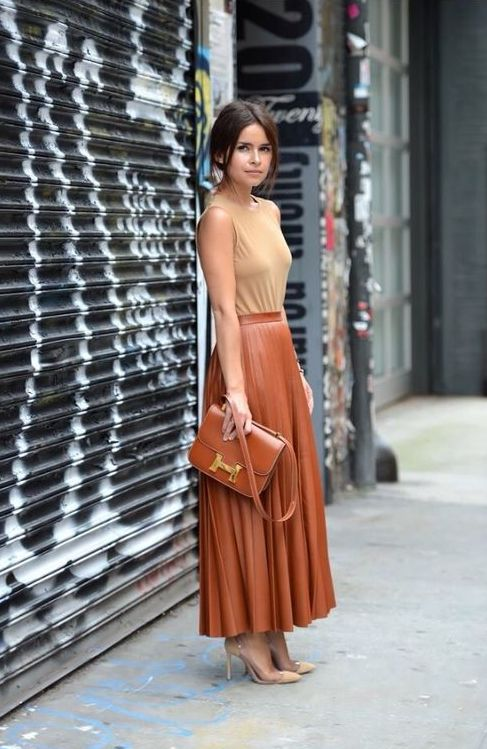 a nude top without sleeves, a cognac-colored midi skirt, nude shoes and a cognac bag