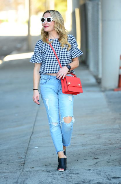 With distressed jeans, black mules and red bag