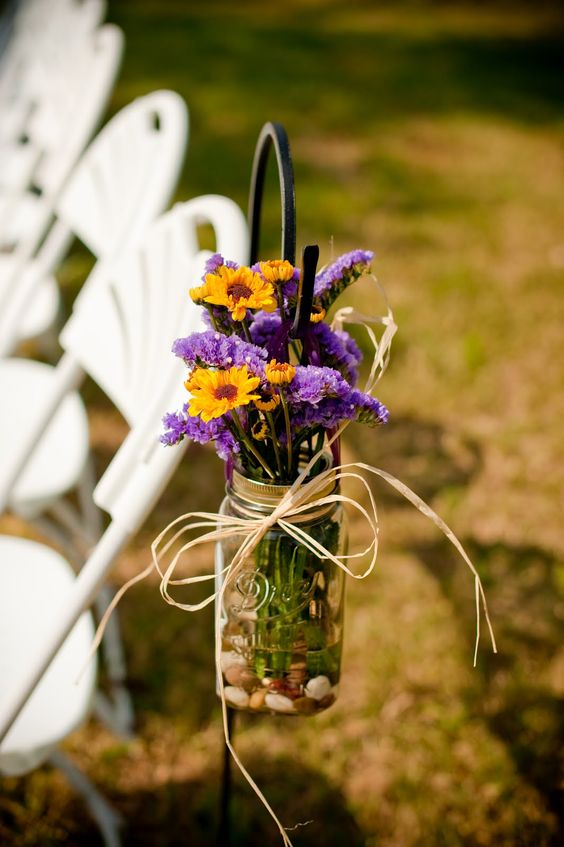 a mason jar with purple and yellow blooms plus twine for wedding aisle decor