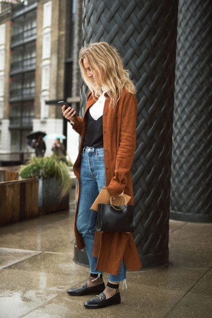 With black top, jeans, flat shoes, black bag and coat