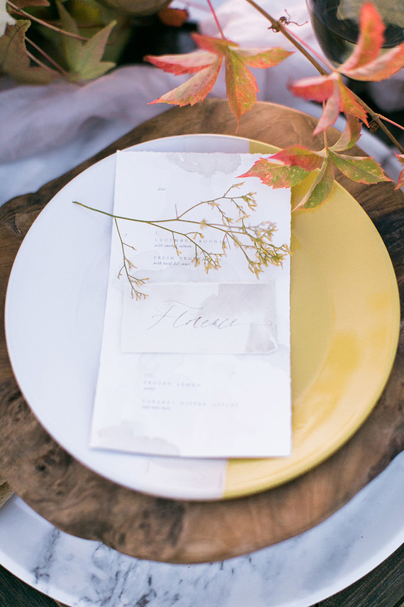 Slight watercolor wedding seating cards and a fall branch decorated the place setting