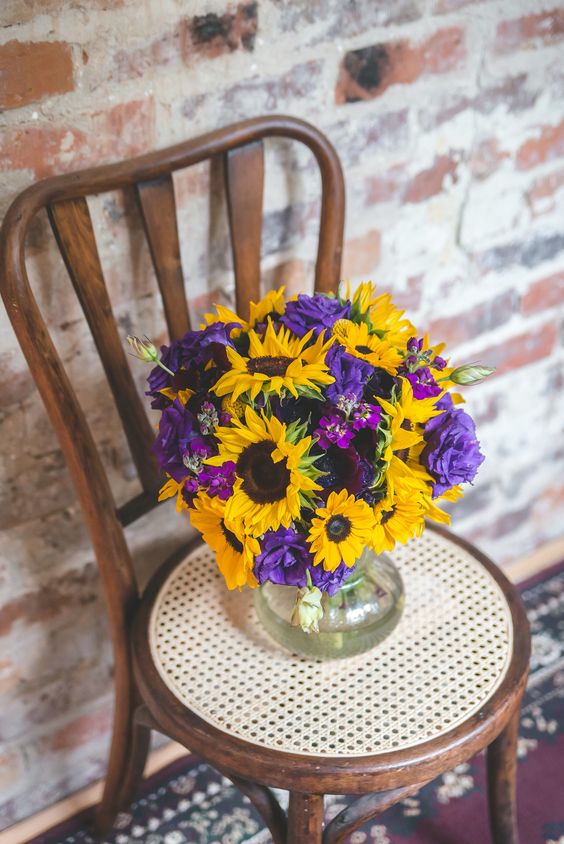 a bold floral centerpiece of purple and yellow flowers for a rustic wedding