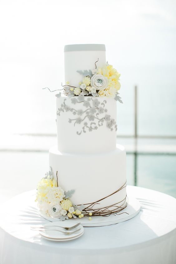 a white wedding cake with grey and yellow sugar flowers and some branches looks ethereal