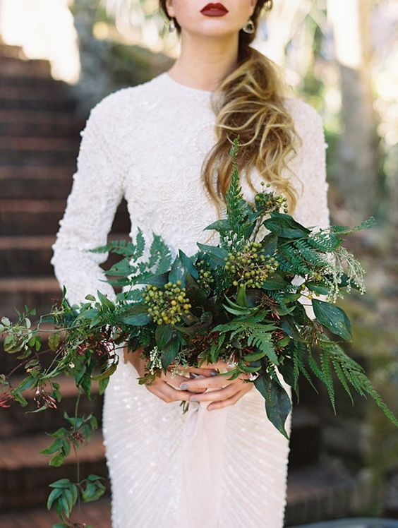 a heavily embellished high neckline long sleeve wedding dress and a lush textural greenery bouquet with berries