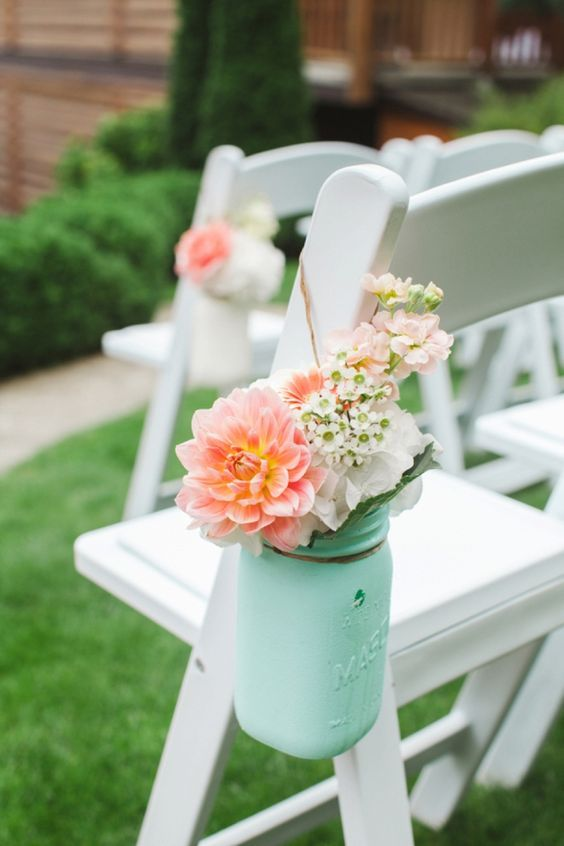 a ceremony space chair with a mint jar and peachy pink flowers in it