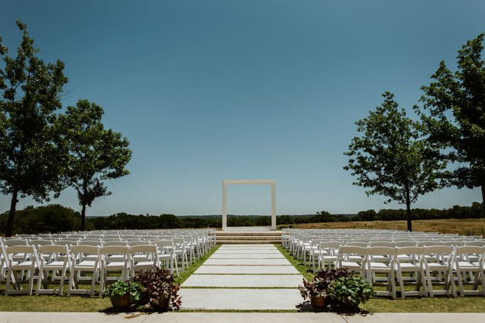 The wedding ceremony space was done with white chairs and a large frame instead of a usual floral arch