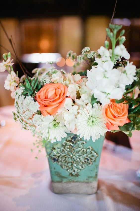 a mint-colored vintage pot with whiote and peachy blooms and a texture