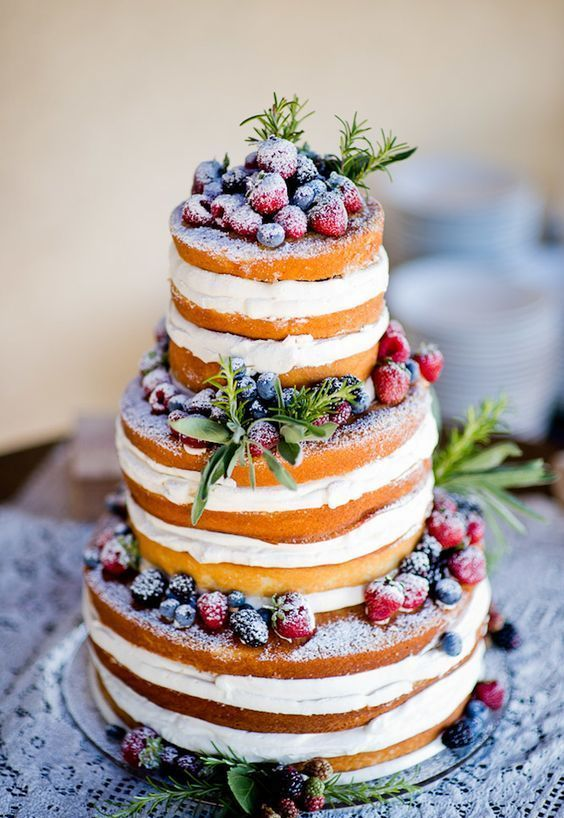 a naked wedding cake with fresh greenery and sugared berries on top is ideal for a rustic wedding