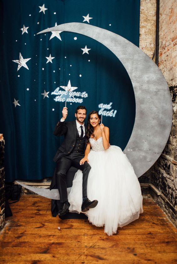 a cute photo booth setting with a crescent moon and stars and matching props for a wedding