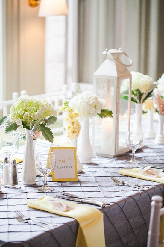 grey and yellow table decor with some floral centerpieces. a white lantern and colored napkins