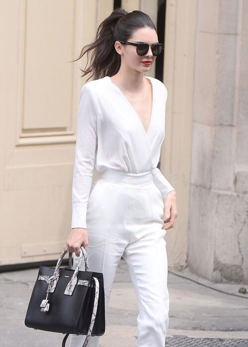 a simple white jumpsuit with long sleeves, a V-neckline, a black bag and a red lip for a statement look