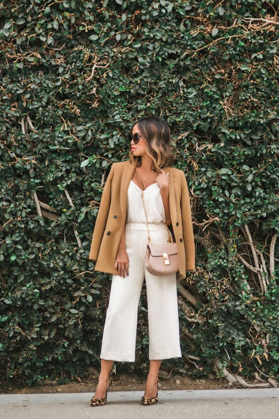 white culottes and a top, leopard shoes, a tan jacket and a blush bag