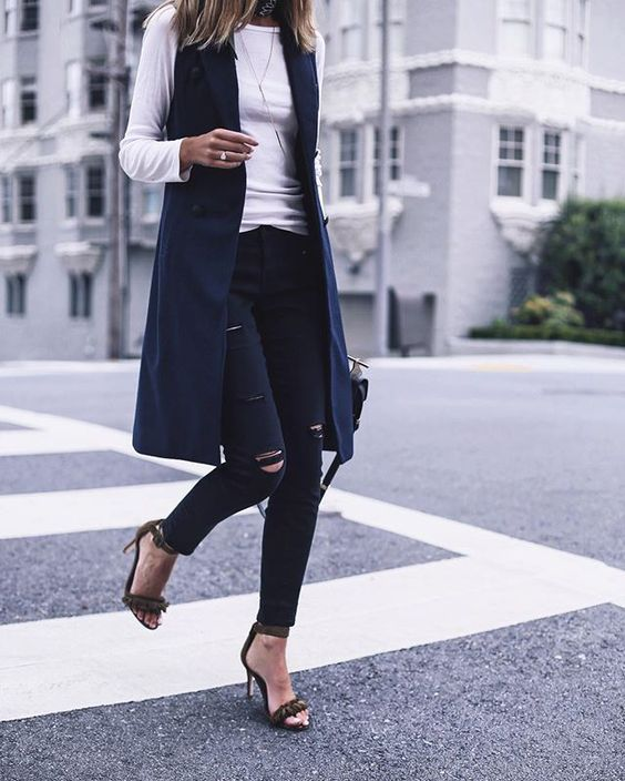 ripped black skinnies, a white long sleeve, a navy long vest and heeled sandals