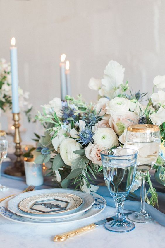 a summer table setting with blue candles, plates and glasses and a floral centerpiece with blue thistles and blush blooms