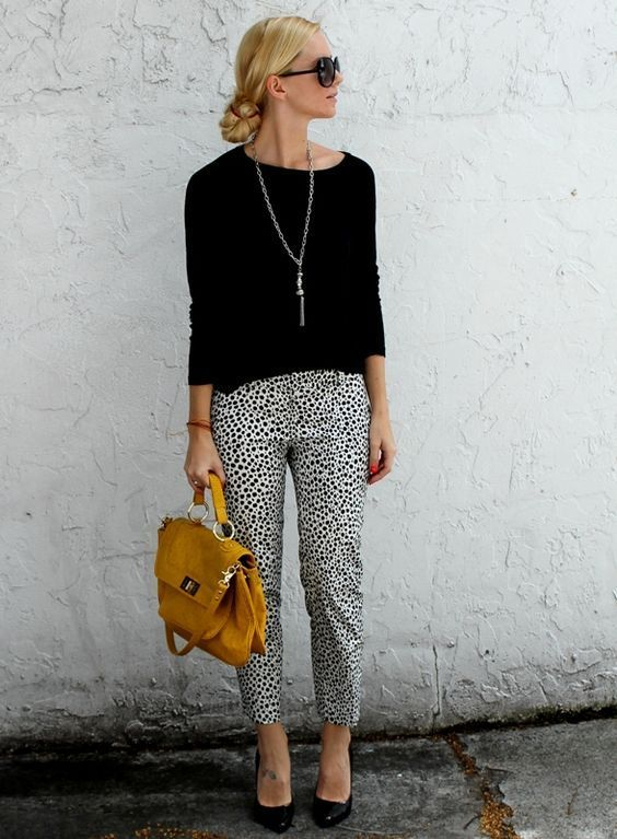 dalmatin printed cropped pants, a black top and heels, a statement necklace and a mustard bag