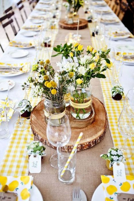 a bold rustic table setting with a checked yellow runner, wood slices and bold yellow blooms for the centerpiece
