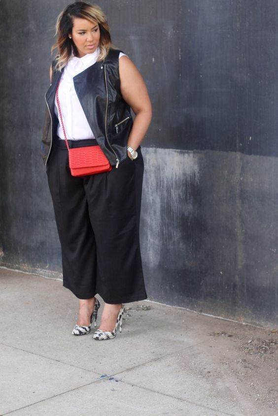 black culottes, a white sleeveless shirt, a black leather vest, a red bag and printed heels