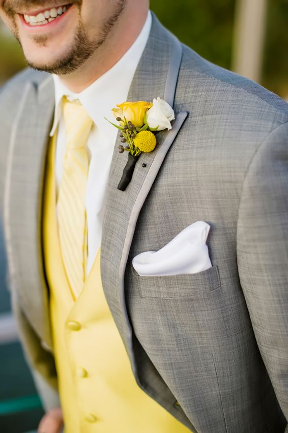 a grey suit with a yellow vest and tie is a chic groom's look for summer