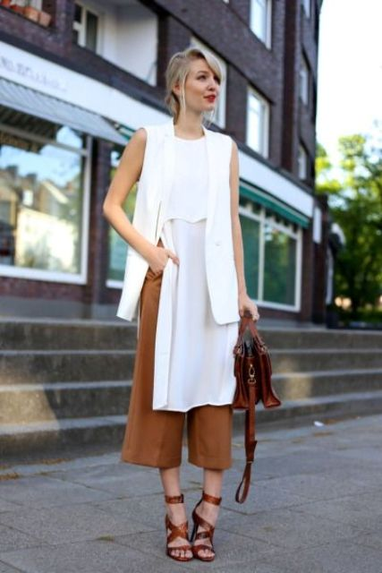 brown culottes, a long white top with a slit, a long white vest, brown strappy shoes and a bag