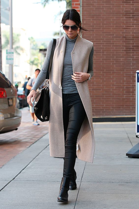 black boots, black pants, a grey turtleneck and a beige long vest for a bold casual look