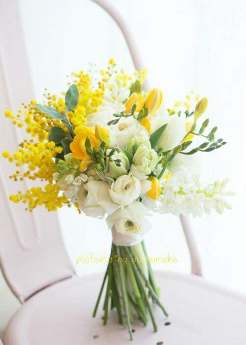 a pretty bouquet with white ranunculus, white and yellow freesia and yellow mimosa